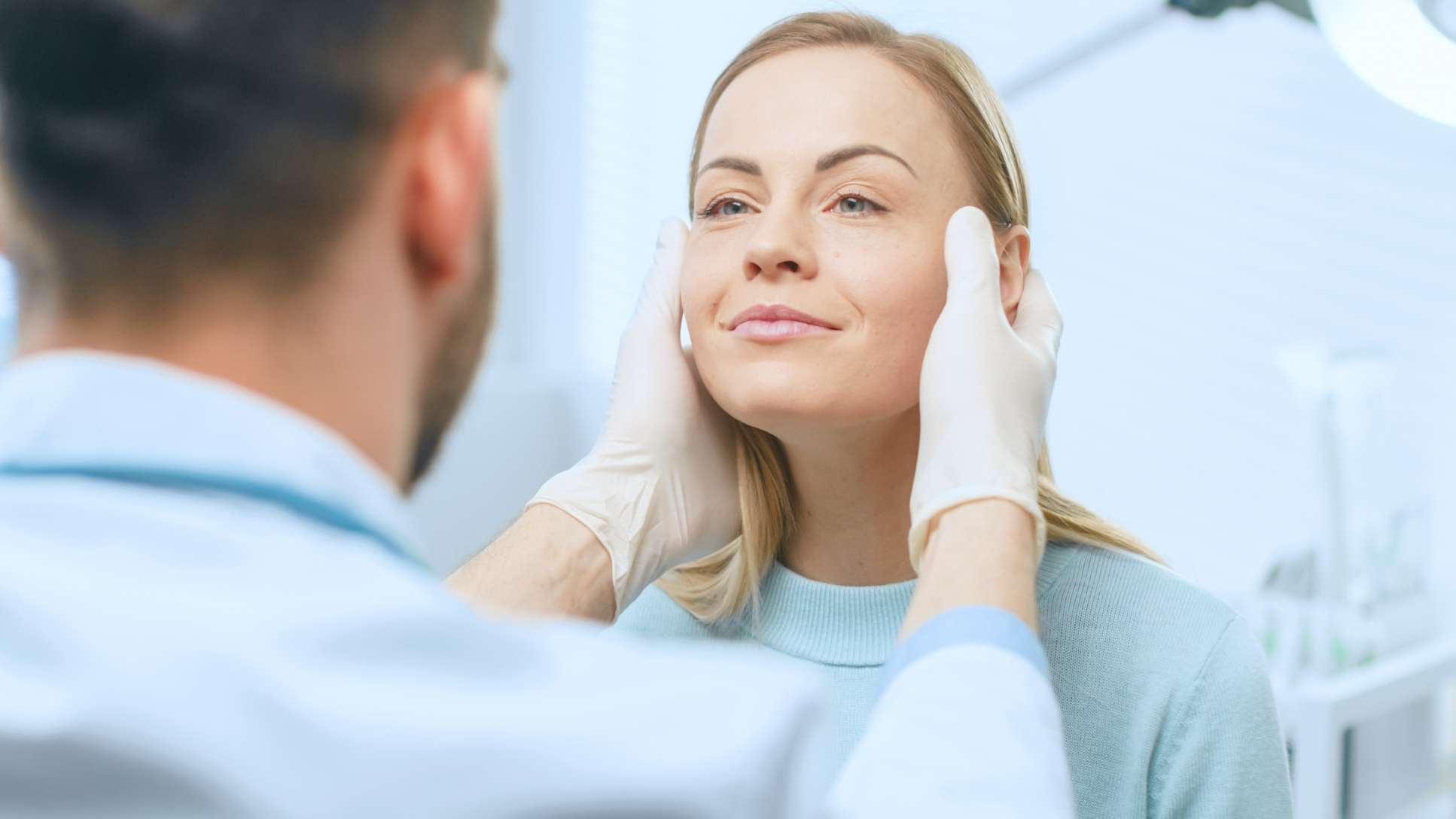 Plastic surgeon examining woman